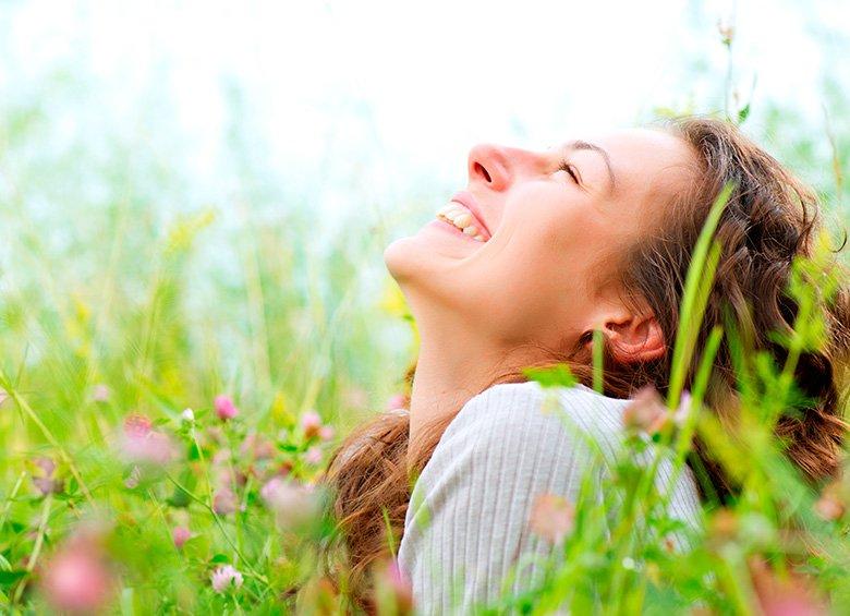 Ragazza di buonumore in un campo di fiori in primavera