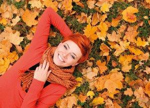 Ragazza dai capelli rossi sorride su un letto di foglie in autunno