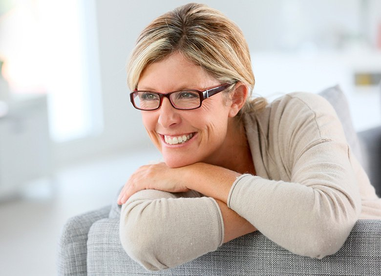 Donna in menopausa sorride seduta sul divano