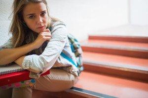 Studentessa seduta sugli scalini con malumore per il rientro a scuola