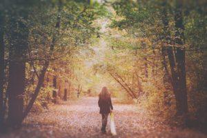 Ragazza cammina in solitaria nel bosco