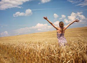 Ragazza apre le braccia in un campo di grano