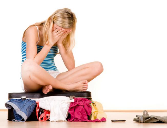 Ragazza seduta su una valigia. Stress da rientro dalle vacanze