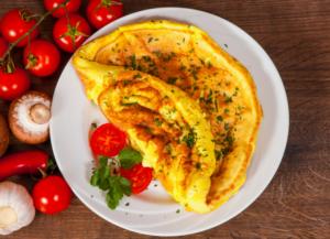 Omelette servita su un ipatto con prezzemolo e pomodorini