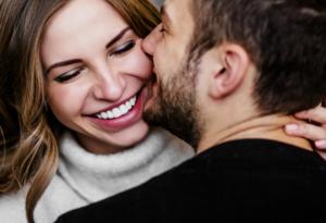 Coppia felice che sorride mentre si abbraccia