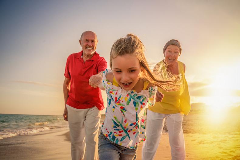 nonni: nonni in vacanza con la nipote passeggiano al mare